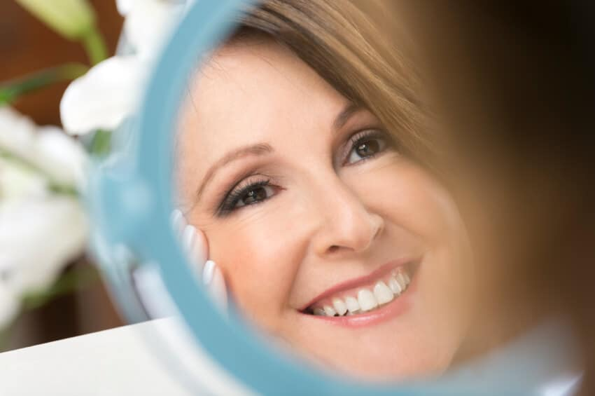 Happy mature woman looking in the mirror